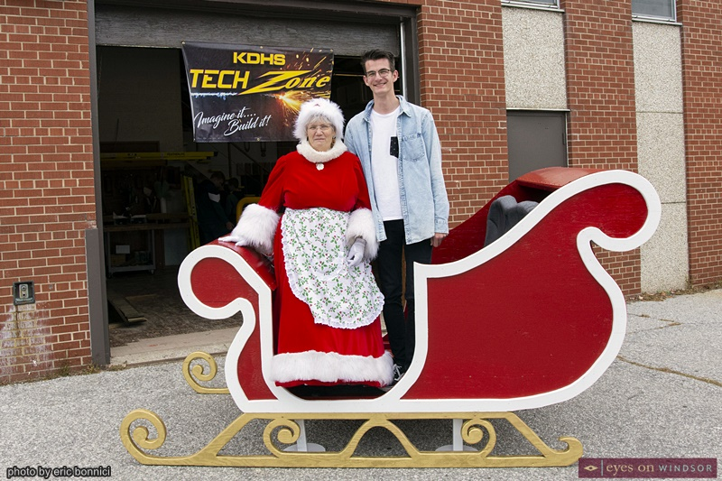 Mrs. Claus and Nickolay Van Eeenschoten standing in Santa's Sleigh