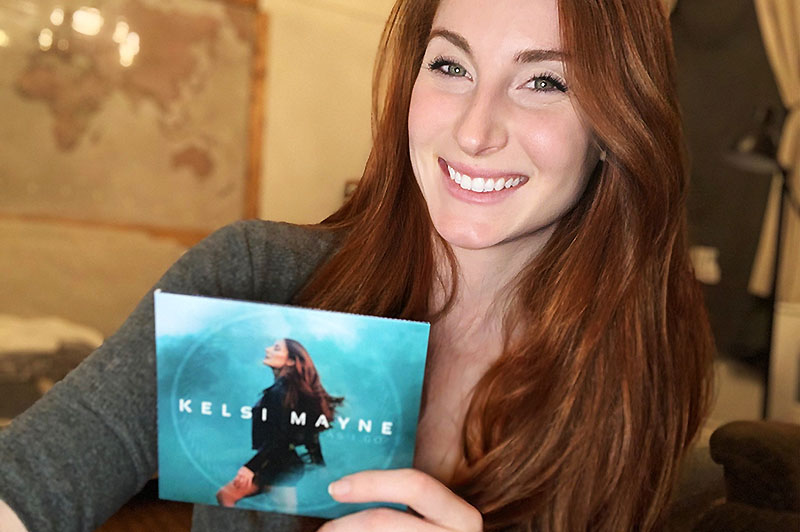 Kelsi Mayne holding her debut album As I Go