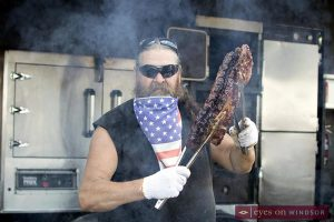 Ribber holding up a rack of ribs at Ribfest Windsor