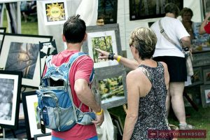 A couple looks at paintings during Art In The Park Windsor.