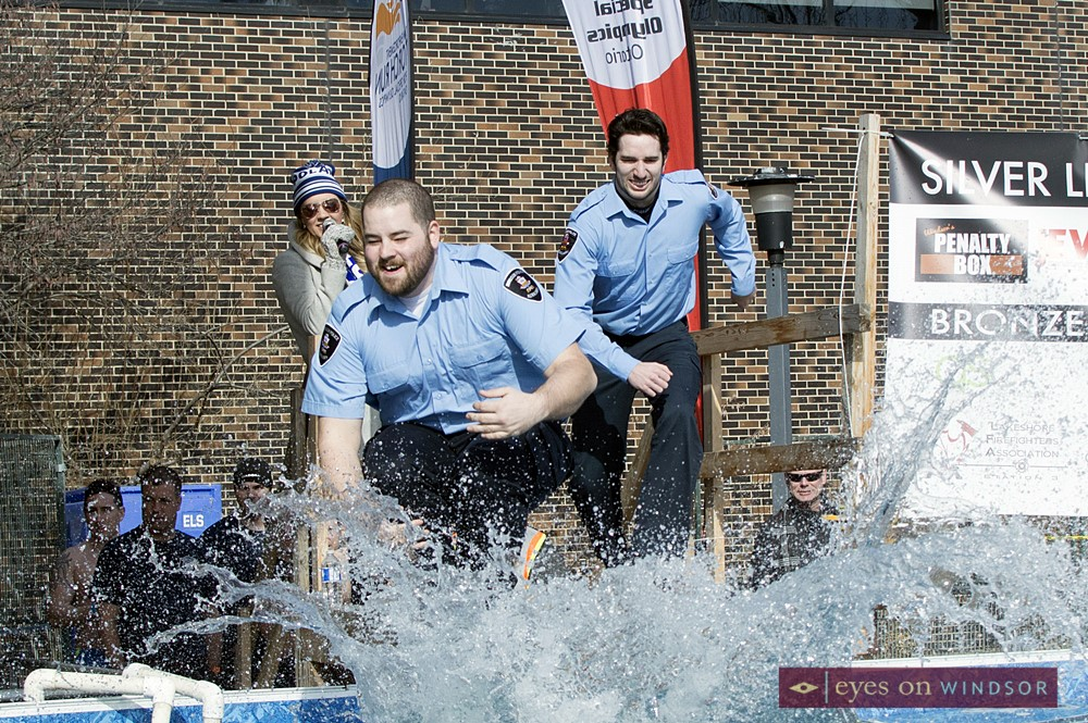 Windsor Police Auxiliary members jump into pool.