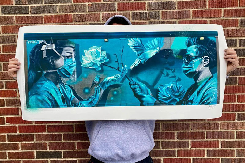 Derkz holding framed healthcare mural print